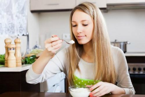 девушка ест творог с йогуртом