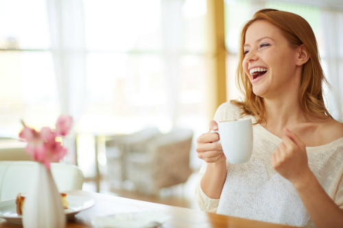 девушка с кофе смеется